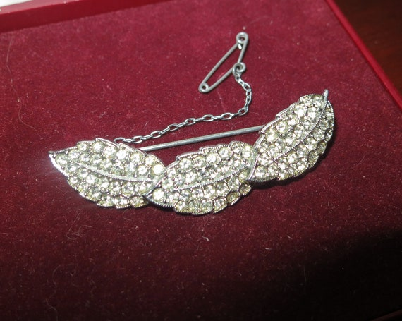 Vintage brooch designed as leaves with many sparkling diamante and safety chain
