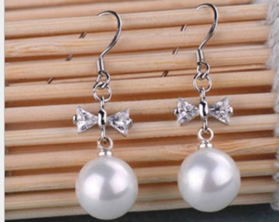 Lovely silver plated 10mm white seashell pearl bow rhinestone earrings