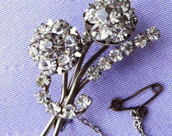 Vintage 1950s silvertone rhinestone flower brooch with safety chain