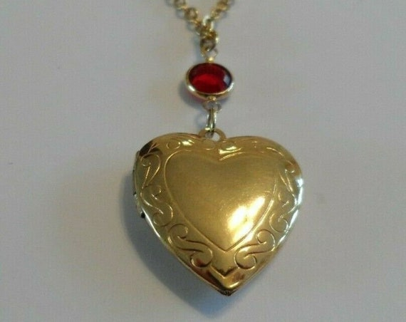 Vintage gold toned metal necklace with opening locket with a ruby red glass stone