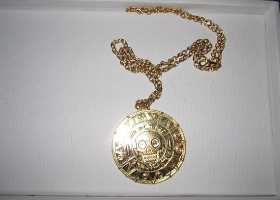 Lovely gold metal necklace with a pirate aztec style pendant