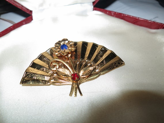 Pretty Coro oriental fan brooch with a flower and red and blue rhinestones
