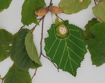A tiny baby doll in a Hazel leaf, cobnut, hazelnuts, Waldorf