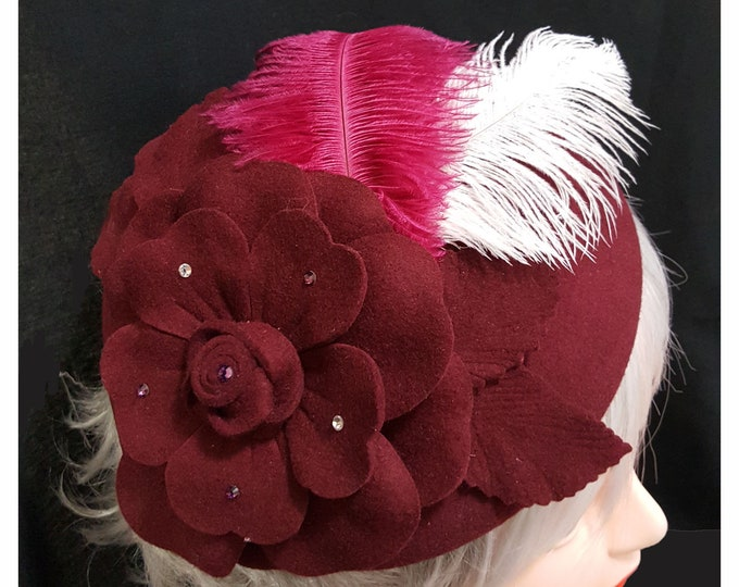 Burgundy Beret wool hat with rhinestone embellishment on flower, accented with feathers.