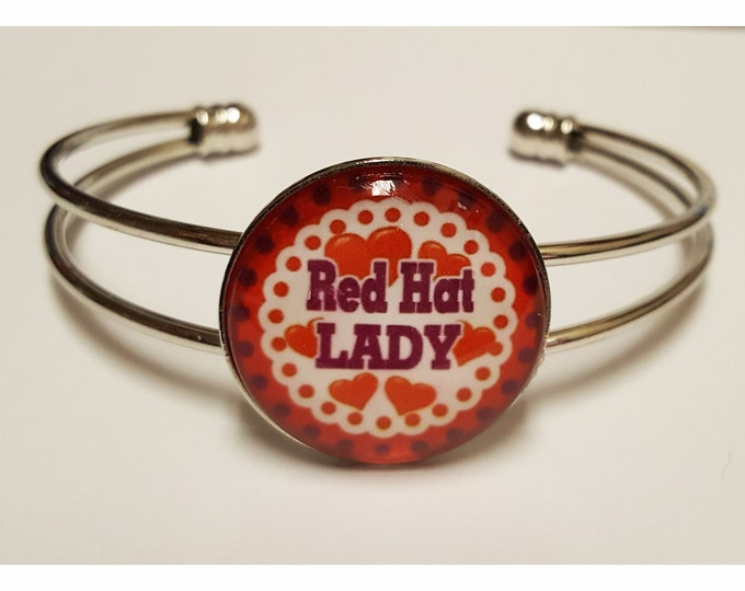 Red Hat Lady Silvertone cuff bracelet with bezel and glass cabochon. Full color image under glass.