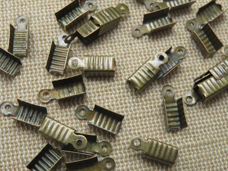 50 Metal knots tone bronze 12x5mm  set of 50 clamp tips to image 0