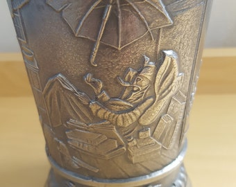 vintage silver coloured beaker depicting life scenes
