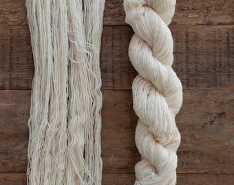 Five skeins of undyed Rambouillet wool fingering weight yarn, single ply, 240 yards, 56 grams per skein