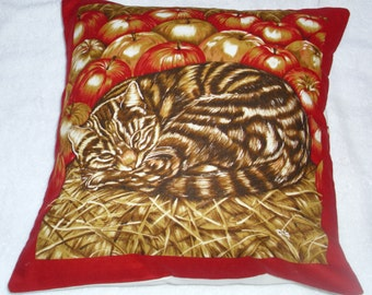 A brown tabby cat curled up in the straw with apples cushion , cotton fabric