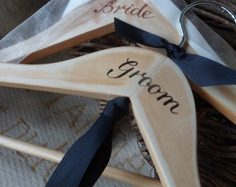 Bespoke wedding hangers... a pair of his and hers wedding hangers with hand painted Bride and Groom. Finished with Grosgrain Bow Ties.