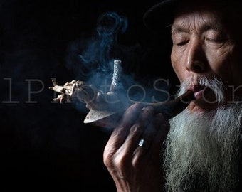 Photo of Chinese pipe master with a crazy pipe in old tea house in Chengdu. China wall art. Smoker portrait. Chinese fine art photography.