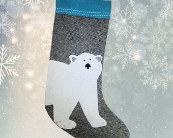 Traditional Christmas stockings with a polar bear pattern sewn on a reclaimed fabric background, rustic hanging gift wrap, handmade