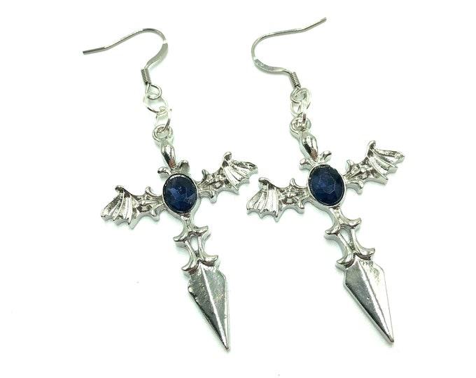 BATTY BEHAVIOR: bat cross earrings with blue accent