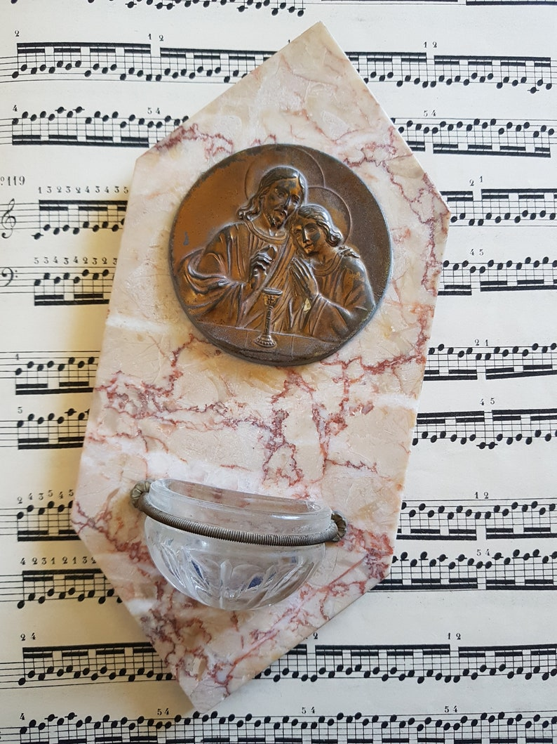 Antique Holy water font on pink marble