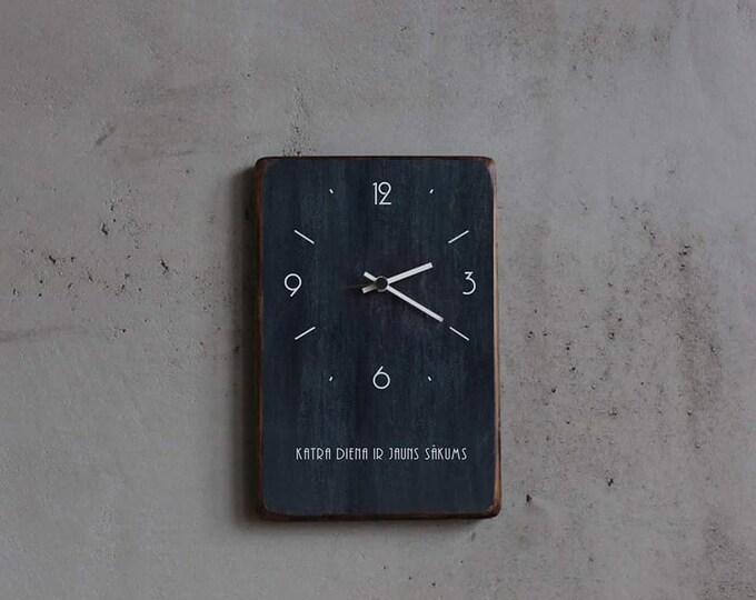 Melns koka pulkstenis ar uzrakstu Katra diena ir jauns sākums