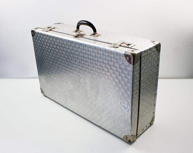 Vintage aluminium suitcase with engraved pattern, steel hardware and leather handle.
