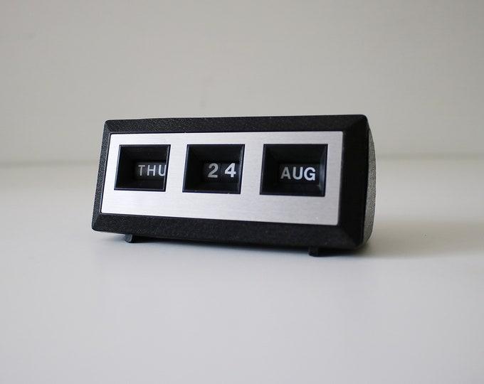 1980s perpetual desk calendar in black textured plastic with silver fascia.