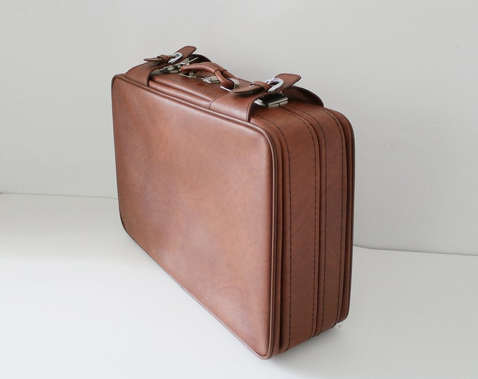 1960s suitcase with buckles and clasps. In tan faux vinyl with black fabric lining. Made by Previdal