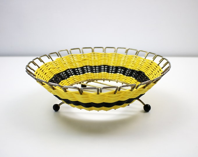 1950s atomic fruit bowl. Gold gilt metal with yellow and black woven plastic. Black bobble feet.