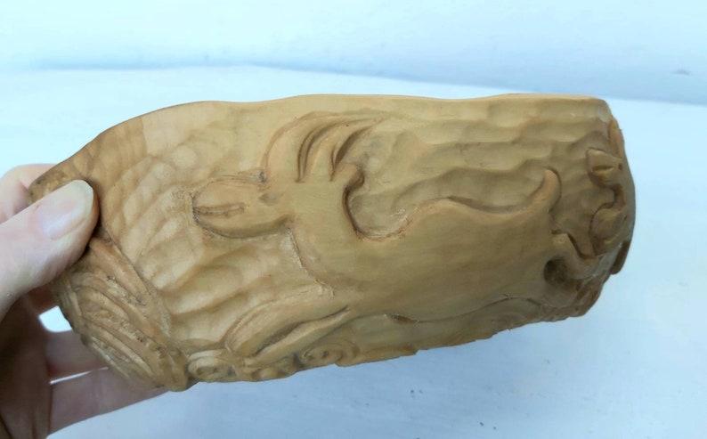 Un bol fait à la main à partir de bois de tilleul en bois, bol sculpté avec la famille de wapiti.