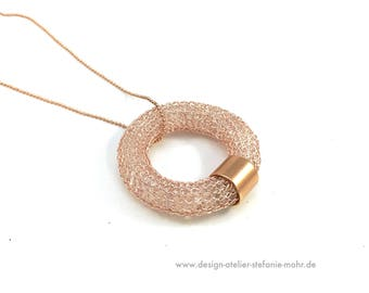 wire crochet rose gold coloured donut/ring pendant filled with rock crystal