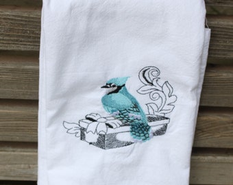 A bird on a gift box is embroidered on a white flour sack tea towel, dish towel, cotton