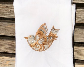 A Christmas Dove is embroidered on a white flour sack tea towel, dish towel, cotton