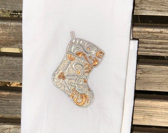 A Christmas Stocking is embroidered on a white flour sack tea towel, dish towel, cotton