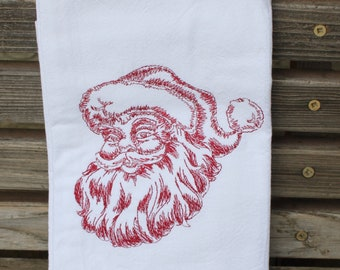 A Beautifully drawn Santa is embroidered on a white flour sack tea towel, dish towel, cotton