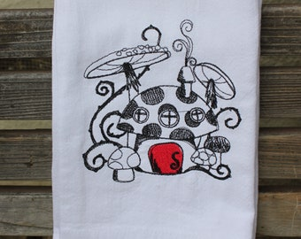 A Beautifully drawn stylized Mr Toad Mushroom house is embroidered on a white flour sack tea towel, dish towel, cotton