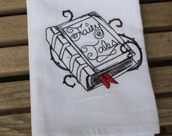 A Beautifully drawn stylized Fairy Tale Book is embroidered on a white flour sack tea towel, dish towel, cotton