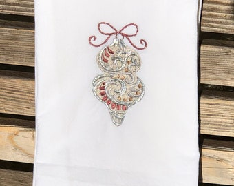 A Christmas ornament is embroidered on a white flour sack tea towel, dish towel, cotton