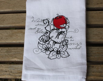 A Beautifully drawn stylized Snow white poison apple is embroidered on a white flour sack tea towel, dish towel, cotton