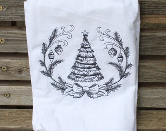 A Beautifully drawn Christmas Tree is embroidered on a white flour sack tea towel, dish towel, cotton