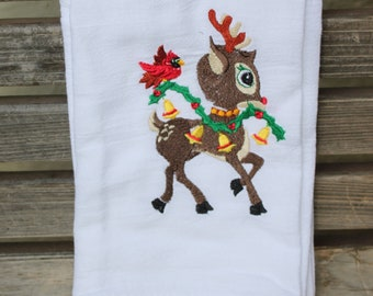 A  Rudolph the red nosed Reindeer is embroidered on a white flour sack tea towel, dish towel, cotton