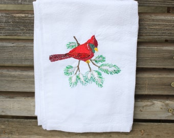 A red winter cardinal on a pine branch embroidered on a white flour sack tea towel, dish towel, cotton