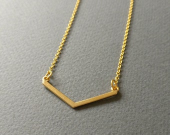Gold toned simple line geometric V necklace.