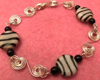 Hand made wire spiralled bracelet with black and white beads