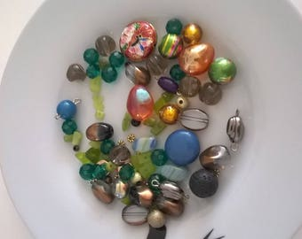Assortment of beads of different materials and shapes and colors