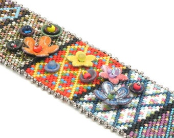 Peyote beaded bracelet with enamel flower bead embellishments