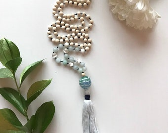 108 bead meditation mala, handknotted with jade and white wood beads. Hand blown glass pendant and cotton tassel.