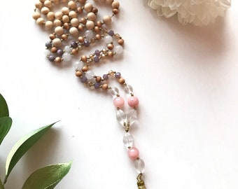 108 bead meditation mala. Handknotted with quartz crystal, pink and white mountain jade. Tassel is gold colored silk.