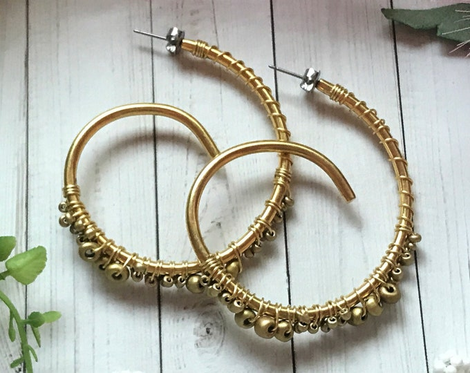 Gold hoop earrings, embellished with golden beads