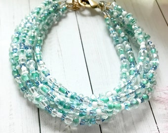 Multi-strand bracelet; adjustable bracelet with glass beads in hues of blue, green and white