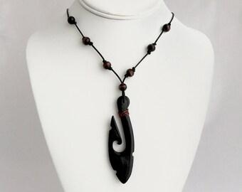 Carved hei matau pendant on beaded leather necklace. A true talisman necklace.