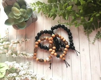 18 bead wrist mala. Choose from black, black & brown, or light wood options. Each with lava bead for essential oils.