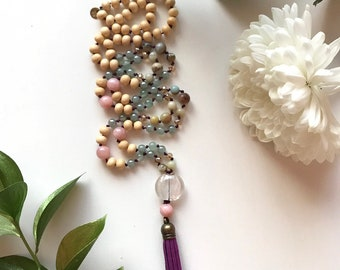 108 bead meditation mala with burgundy leather tassel. Beads are white wood and pink mountain jade.
