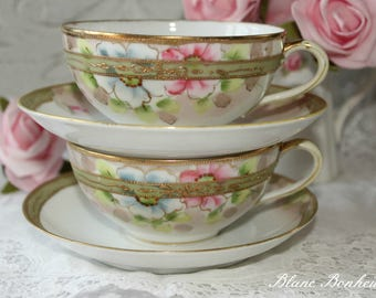 Nippon, Japan: set of two tea cups and two saucers, in white, blue, pink and gold