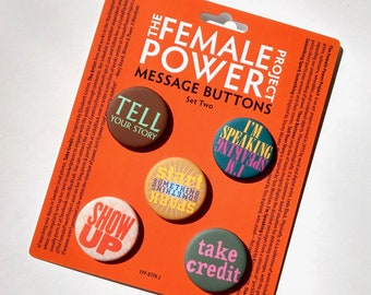 SET TWO: feminist messages on five pin-back buttons on information card