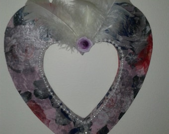 Beautiful decoupaged heart adorned with beads, purple flowers and feathers.